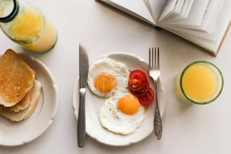 Photo for Top view of book and breakfast with fried eggs and orange juice, isolated on white - Royalty Free Image
