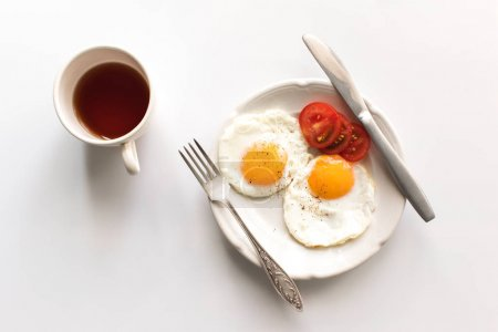 Photo for Top view of breakfast with fried eggs on plate and tea, isolated on white - Royalty Free Image