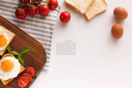 Photo for Top view of breakfast with fried eggs on toasts and tomatoes on cutting board - Royalty Free Image