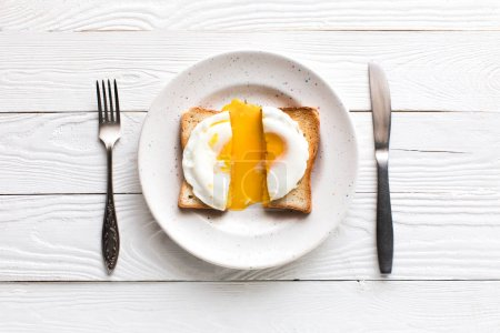 Photo for Top view of breakfast with fried egg on toast on plate on wooden tabletop - Royalty Free Image