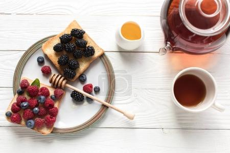 Photo for Top view of breakfast with fresh berries on toasts and tea on wooden tabletop - Royalty Free Image