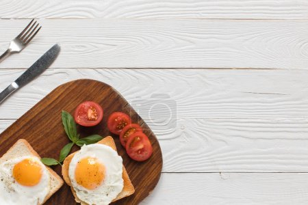 Photo for Top view of breakfast with fried eggs on toasts and tomatoes on wooden tabletop - Royalty Free Image