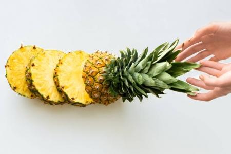 Photo for Top view of hands with sliced fresh pineapple, isolated on white - Royalty Free Image