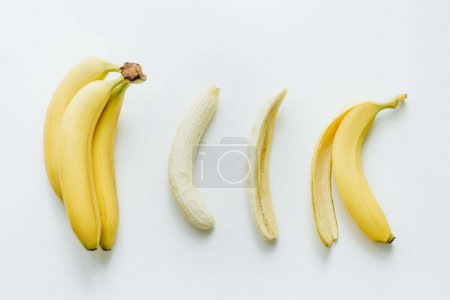 Photo for Top view of tropical yellow bananas lying in row, isolated on white - Royalty Free Image