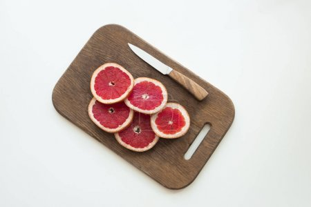 Photo for Top view of fresh sliced grapefruit and knife on wooden cutting board, isolated on white - Royalty Free Image