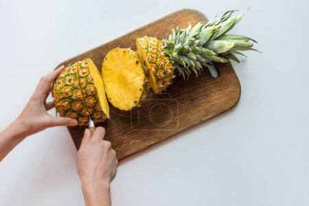 person cutting pineapple