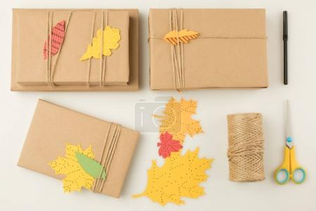 Photo for Top view of handmade wrapped gifts, scissors, handcrafted paper leaves and marker isolated on beige - Royalty Free Image