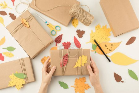 Photo for Cropped shot of female hands holding handmade wrapped gift with paper leaves, scissors and rope roll around isolated on beige - Royalty Free Image