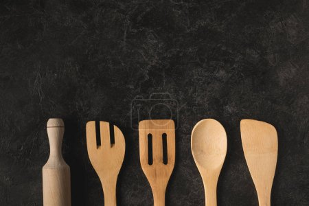 Photo for Flat lay with arranged wooden kitchen utensils isolated on black tabletop - Royalty Free Image