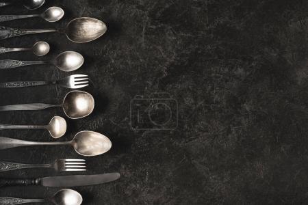 Photo pour Vue de dessus de l'ensemble d'argenterie vintage isolé sur table noire - image libre de droit