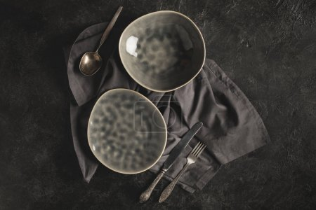 Photo for Top view of ceramic plates and rustic silverware on linen isolated on black surface - Royalty Free Image