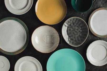 Photo for Top view of various arranged ceramic plates isolated on black surface - Royalty Free Image