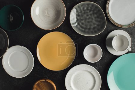 Photo for Flat lay with ceramic plates, cup on saucer and jug isolated on black table - Royalty Free Image
