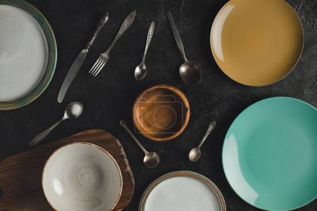 Photo for Flat lay with arranged ceramic plates, antique silverware and cutting board isolated on black surface - Royalty Free Image