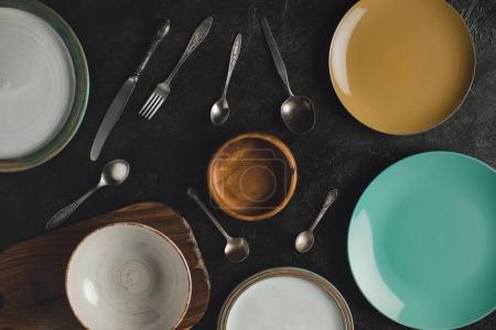 Photo pour Lay plat avec plaques en céramique disposées, argenterie antique et planche à découper isolées sur la surface noire - image libre de droit