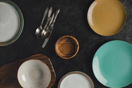 Foto de Endecha plana con placas de cerámica dispuestas, plata antigua y tablero de corte aislado en superficie negra - Imagen libre de derechos