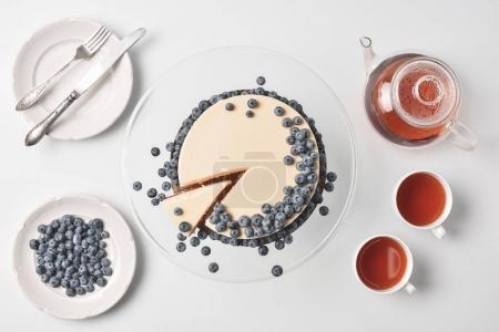 Photo for Top view of sliced cheesecake with blueberries on glass stand with tea and tableware - Royalty Free Image
