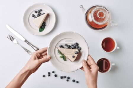 woman serving cheesecake with blueberries on table