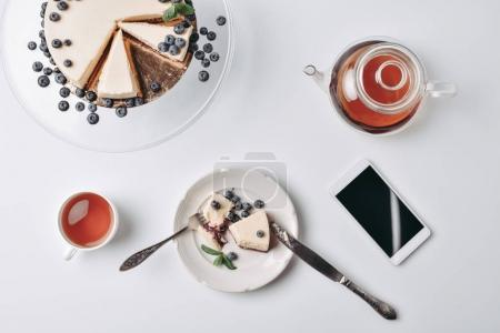 Photo for Top view of slice of cheesecake with blueberries and tea on table - Royalty Free Image