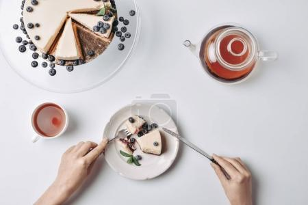 Photo for Top view of woman eating cheesecake with blueberries with fork and knife - Royalty Free Image