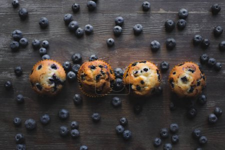 Photo for Top view of tasty healthy muffins with fresh blueberries on wooden table - Royalty Free Image