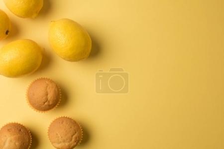 Photo pour Vue de dessus des muffins frais faits maison avec des citrons isolés sur jaune - image libre de droit