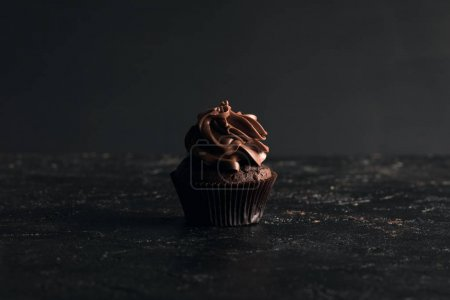 Photo for Close-up view of sweet homemade chocolate cupcake on black - Royalty Free Image