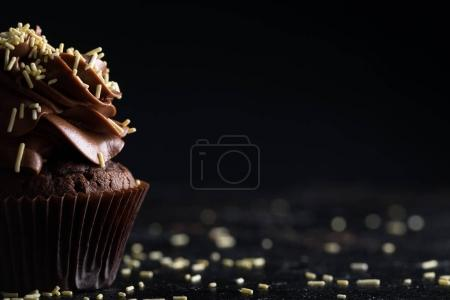Photo for Close-up view of tasty homemade chocolate cupcake with icing on black - Royalty Free Image