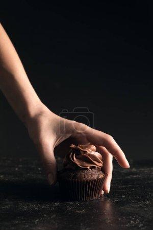 Hand with chocolate cupcake