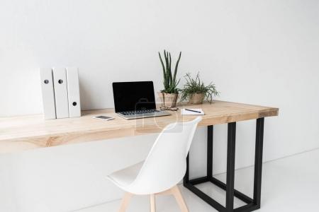 Foto de Lugar de trabajo con ordenador portátil y las carpetas en la oficina moderna - Imagen libre de derechos