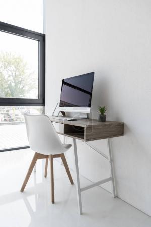 Photo pour Lieu de travail avec ordinateur et pot de fleurs dans le bureau moderne - image libre de droit