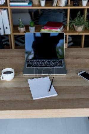 Photo pour Lieu de travail avec ordinateur portable et bloc-notes vierge dans le bureau moderne - image libre de droit
