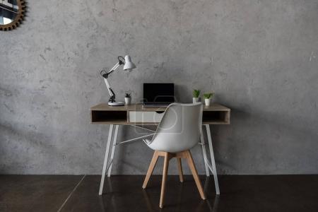 Foto de Lugar de trabajo con ordenador portátil y poco los potes de flor de oficina moderna - Imagen libre de derechos