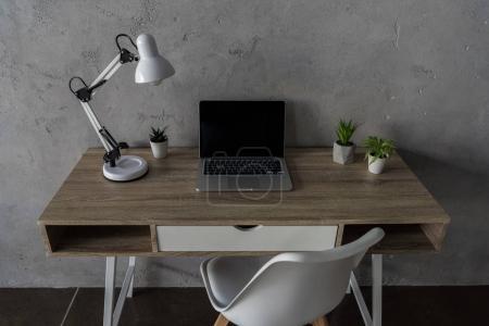 Photo pour Lieu de travail avec ordinateur portable, table lampe fleur pots et dans les bureaux modernes - image libre de droit
