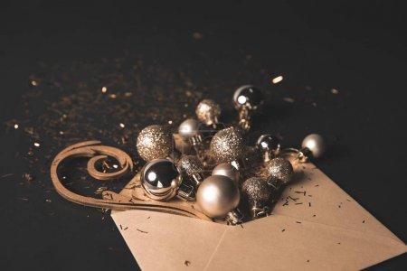 Photo pour Boules de Noël dorées dans une enveloppe kraft sur fond noir - image libre de droit