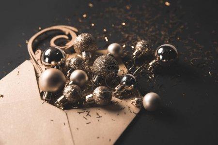 Photo pour Boules de Noël dorées et confettis dans une enveloppe kraft sur fond noir - image libre de droit
