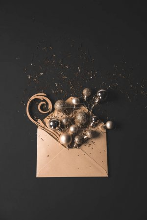 Photo for Golden christmas balls in kraft envelope on black with copy space - Royalty Free Image