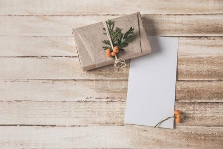 Photo for Empty Christmas card and present with rowan decoration on shabby wooden tabletop - Royalty Free Image