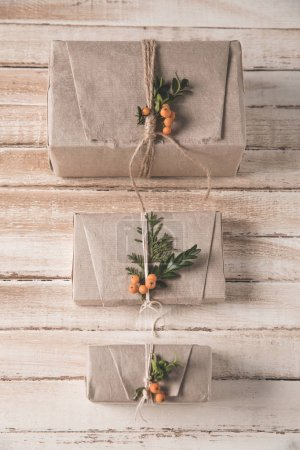 Photo for Christmas presents in craft paper with rowan decoration lying in row on shabby wooden tabletop - Royalty Free Image