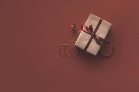 Photo for Christmas kraft gift box with ribbon, isolated on red with copy space - Royalty Free Image