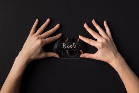 hands with halloween cookie