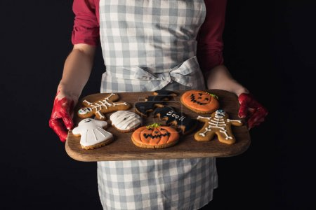 girl holding tray with halloween cookies