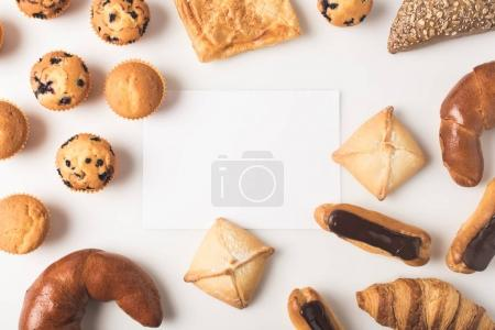 Photo for Flat lay with various types of pastry and blank card isolated on white - Royalty Free Image