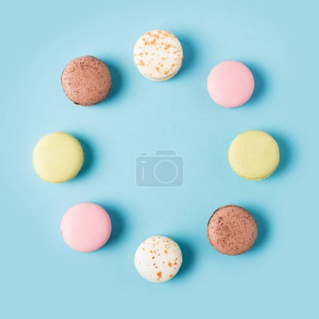 Photo for Flat lay with arranged various sweet macarons isolated on blue - Royalty Free Image