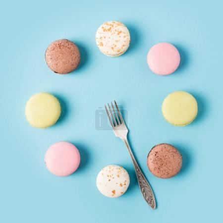 Photo for Flat lay with arranged sweet macarons and silver fork isolated on blue - Royalty Free Image