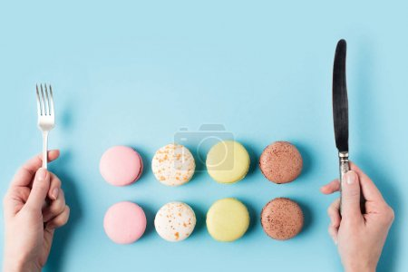 Macarons and female hands with silverware