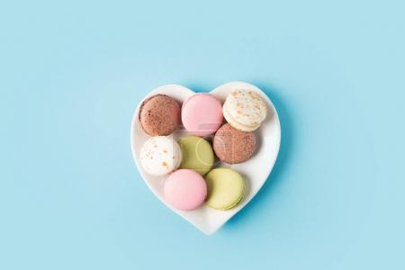 Photo for Top view of macarons on heart shaped plate isolated on blue - Royalty Free Image