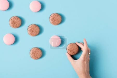 Photo for Close up view of female hand and sweet macarons isolated on blue - Royalty Free Image