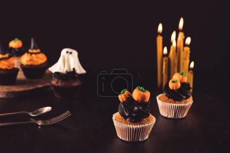 Photo pour Vue rapprochée de délicieux cupcakes fantomatiques d'Halloween et de bougies allumées sur noir - image libre de droit