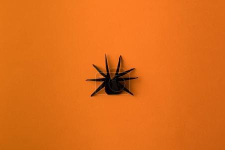 Foto de Una araña de origami negro de halloween, aislado en naranja - Imagen libre de derechos